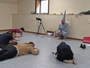 People sitting on floor in workshop