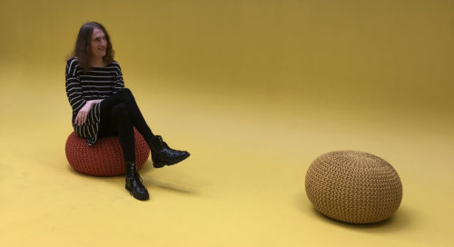 A person with long har sits on a round cushion on a yellow floor, against a yellow backdrop