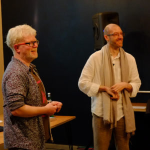 Two men standing about to give a presentation