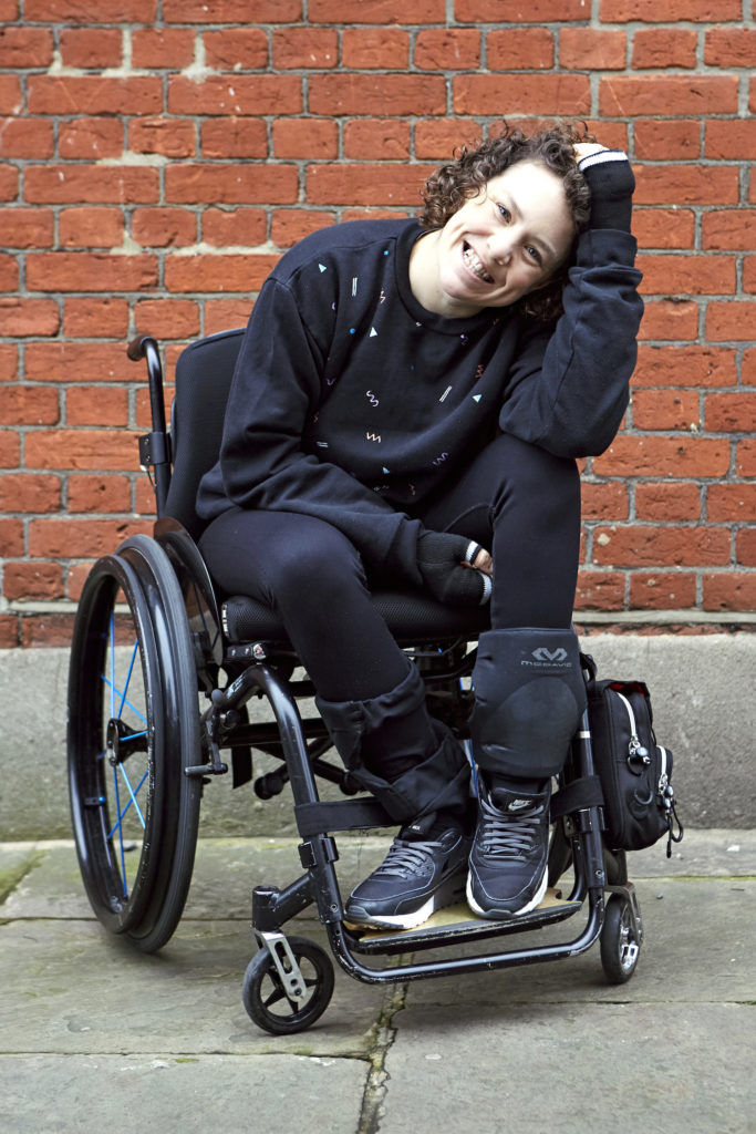 a young white female wheelchair-user is portrayed against a red brick wall