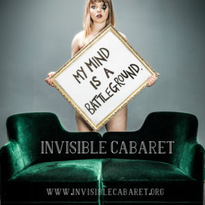 A young woman stands naked behind a green sofa bearing a placard