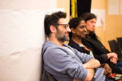 a male actor and two female actors sit against a wall, side by side, smiling