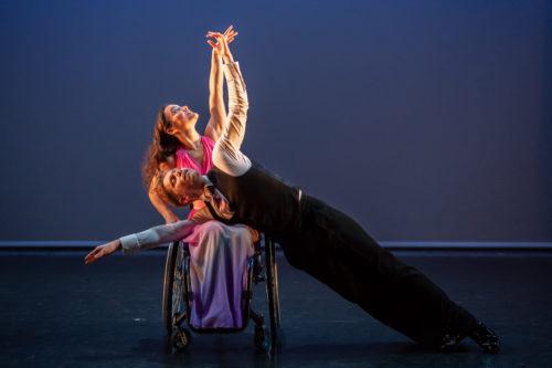 Man rests on knees of wheelchair dancer
