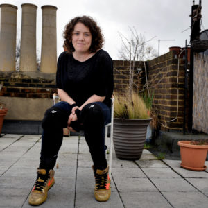 a young white female sits in a chair on a rooftop garden