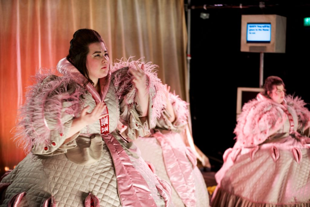 an actor in a large pink dress stands centre-stage