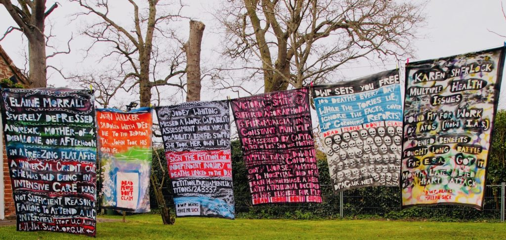 6 shrouds with painted text hanging in a line outside with trees in the background