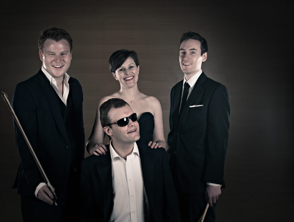 sepia tinted image of four musicians dressed in smart evening wear