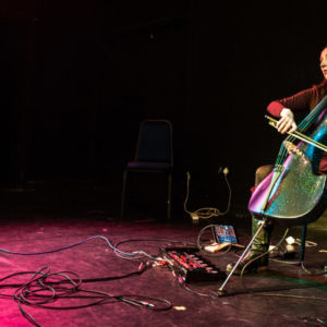 Image shows Jo-Anne playing cello on a black stage, with a red spotlight. Photo credit: Oliver Cross