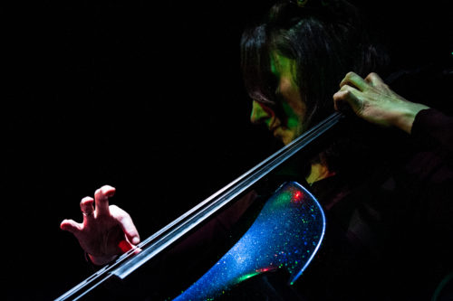 Close up of Jo-anne plucking the strings of her purple sparkly cello in atmospheric dark background.