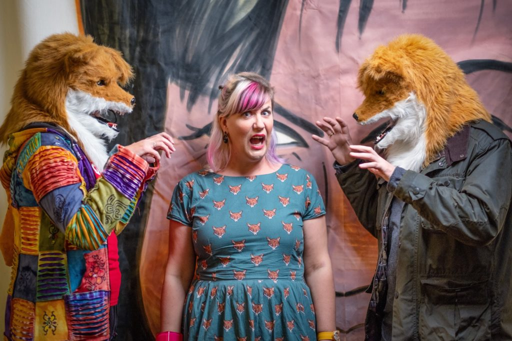 A young woman stands on stage between two actors dressed in fox costumes