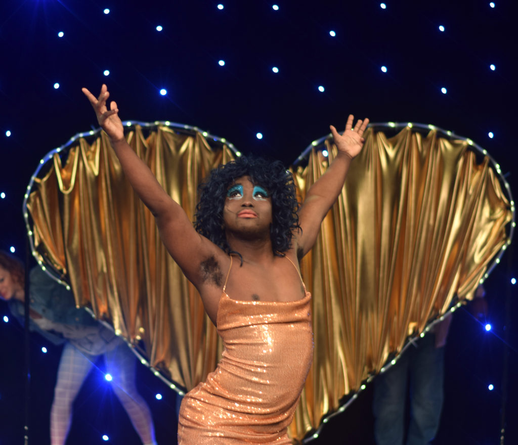 a black trans person poses in a glittery dress