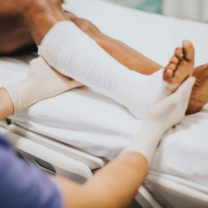 a man's broken leg is being wrapped in bandages by a medic