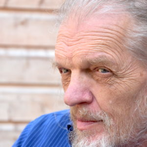 A an older man's face looks away from the camera against the backdrop of a brick wall
