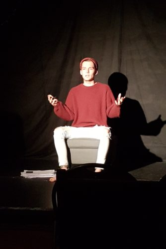 young white male wearing a red top and beanie sits on a darkened stage