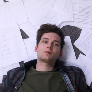 a young white male lies down his head on a bed of papers