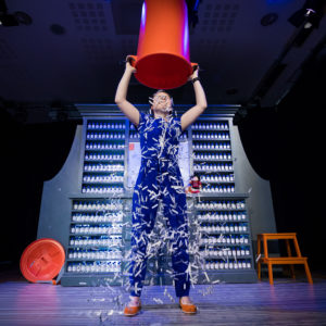 a woman in a blue suit stands pouring a bucket of syringes over her head