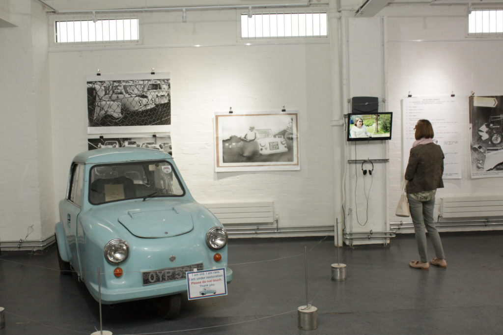 A light blue NHS invalid carriage is pictured in a gallery space with large photogrpahs on the wall behind it