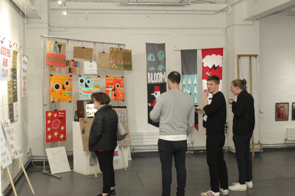 Placards, posters and brightly coloured artworks hanging on a frame are pictured in a gallery space