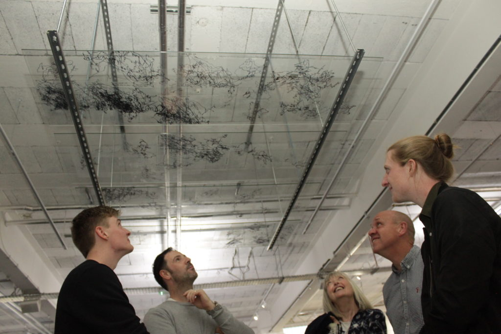 a group of people look up at a series of black line drawings on glass