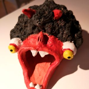 bright red sculpture of a monster with a large red mouth