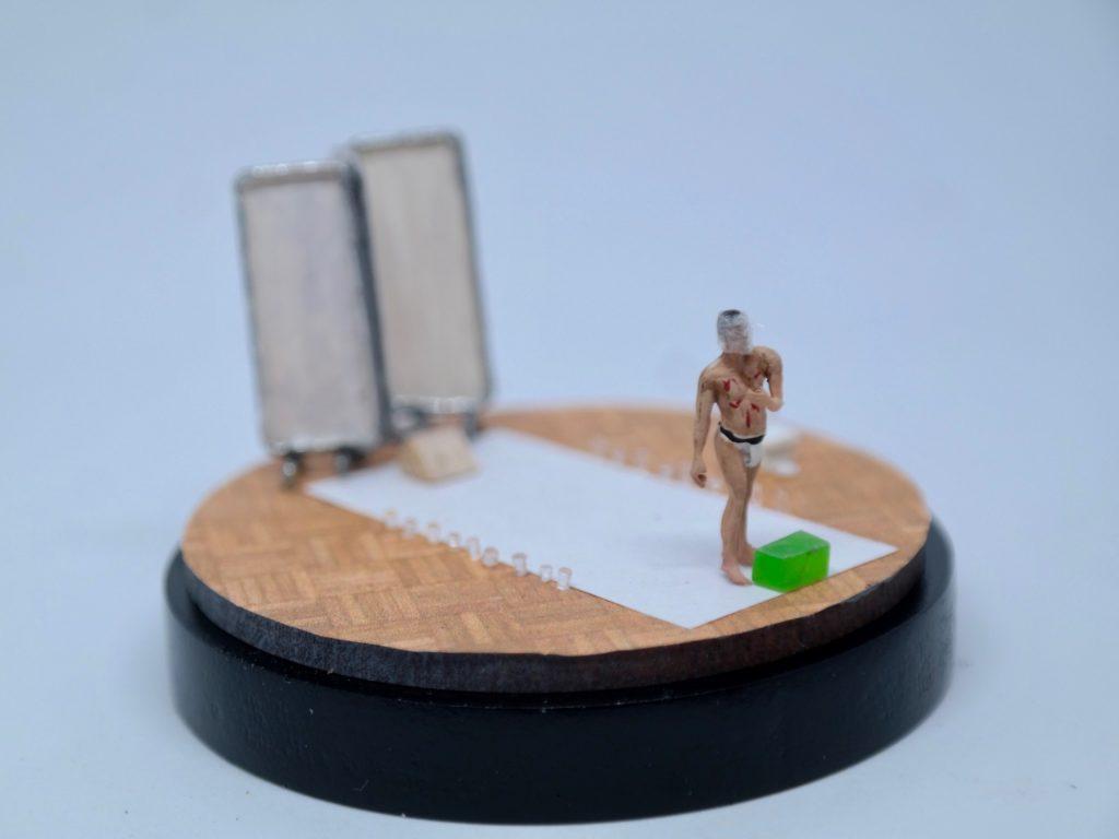 Diorama of man walking down white carpet