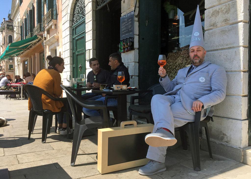 Man in grey suit drinking aperol spritz