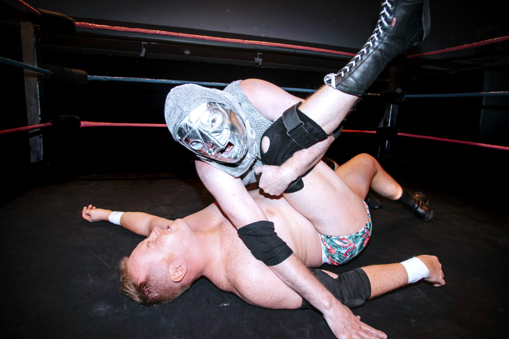 a hooded wrestler fights inside the ring