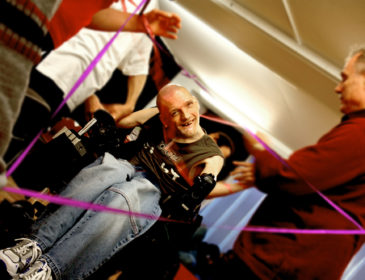 photo of a smiling disabled man in a wheelchair