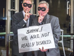 two men with masks hold a banner