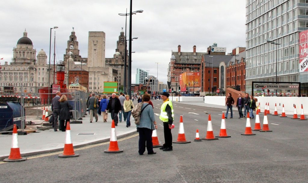 artist wearing a hi-viz jacket stands in a main road having blocked it with traffic comes