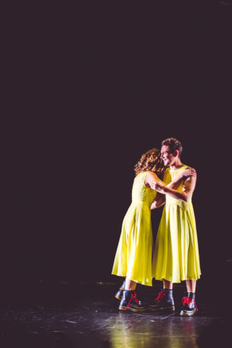 a man and a woman dressed in bright yellow dresses and doc martens with red laces hold each other on stage