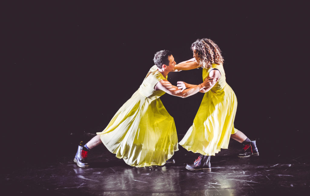 a man and a woman dressed in bright yellow dresses and doc martens with red laces grapple each other on stage