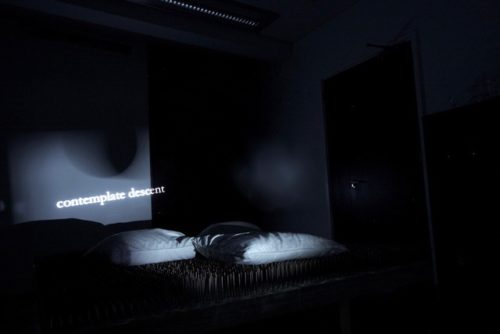 abstract projected image of bed of nails and projected text