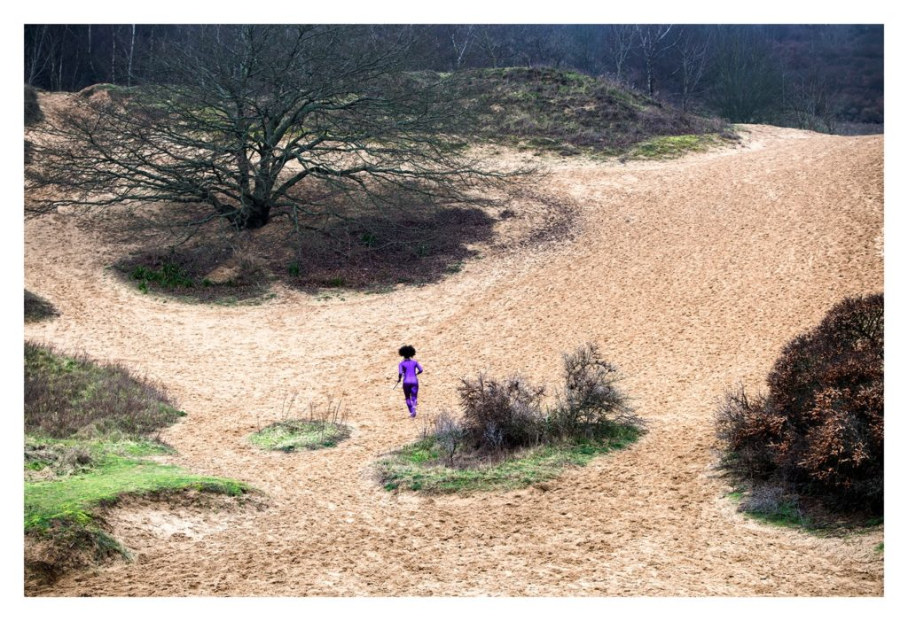 Woman running across a landscape