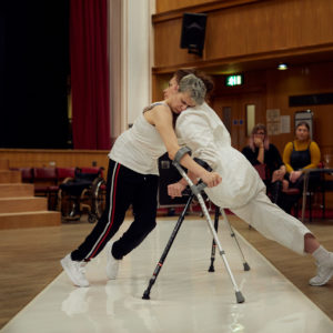 Two female crutch users balance against each other