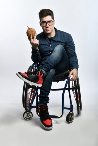 Wheelchair user holding a coconut