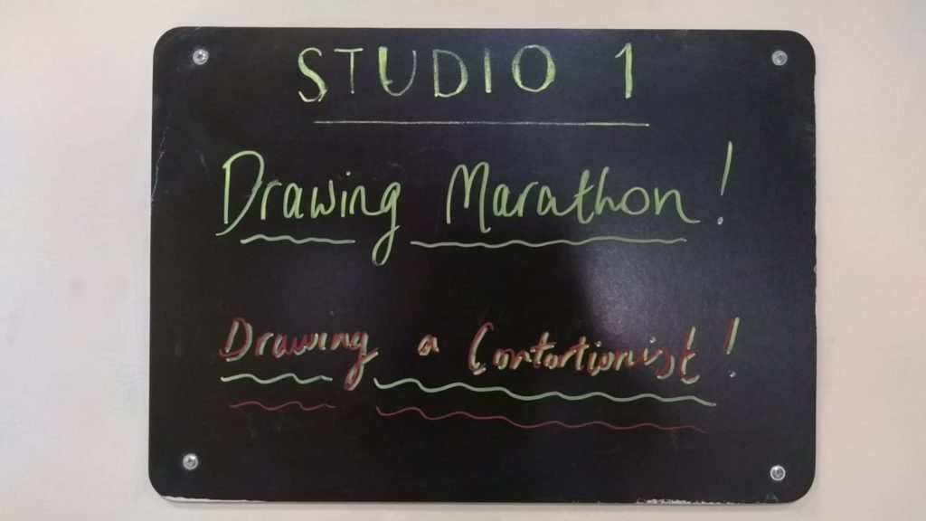 Small blackboard with the words: Studio 1. Drawing MArathon! Drawing a Contortionist.