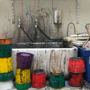 messy sink with colourful ink splattered water pots