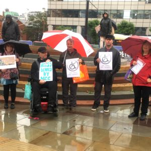 a group of disabled people protest in front of an inaccessible memorial