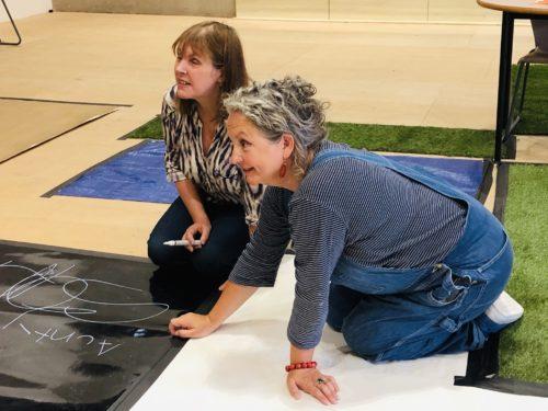 Two women crouching on floor