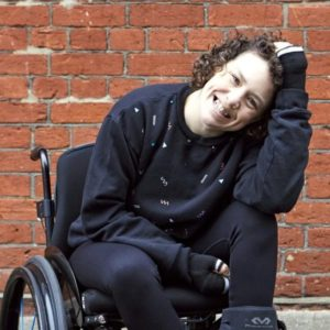 Woman in all black sitting in a wheelchair