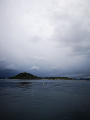 A large body of water, a small island on the horizon and a moody grey sky