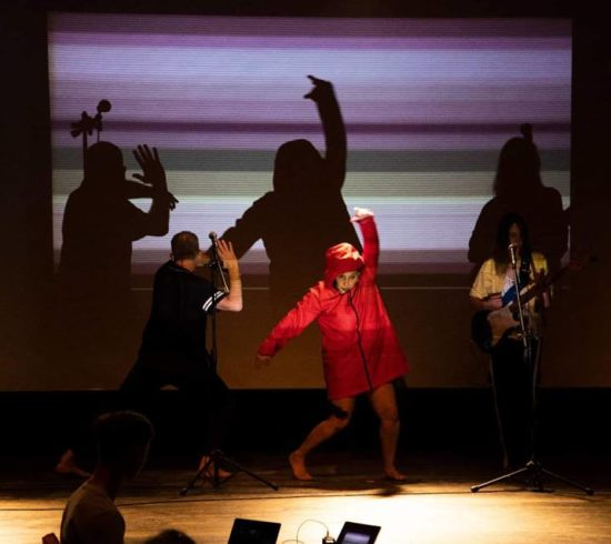Three dancers from Signdance Collective signing on stage, lit by a projection