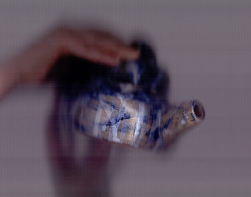 A blue, white, and grey wonky hand made teapot is held up by a white persons hands. The whole image is slightly out of focus and the hands are blurred