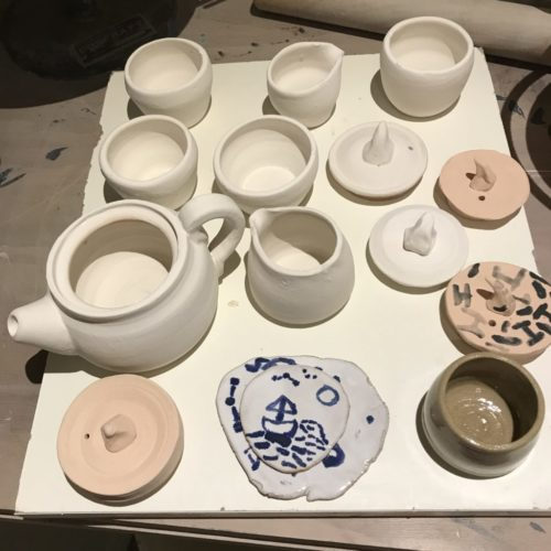 a hand made tea set consisting of one teapot, four cups, two jugs and a sugar basin are covered in white glaze ahead of firing. We also see some glazing samples and 3 unfinished lids.