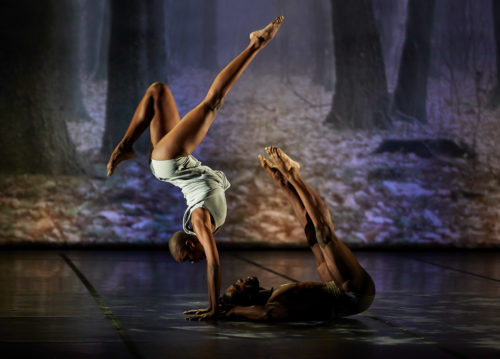 A dancer wearing a grey sleeveless top and shorts performing a handstand with one leg bent and one outstretched. Another person lays below them on their back with their legs outstretched into the air.