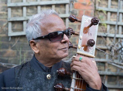 Indian man holds a sitar by the neck