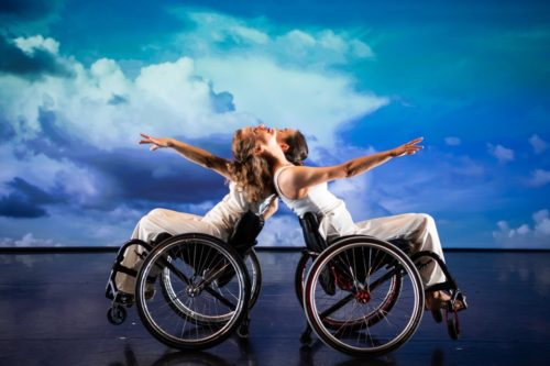 Two wheelchair dancers balancing against each other as they lean back