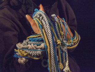 Person holding a mess of ropes in different colours