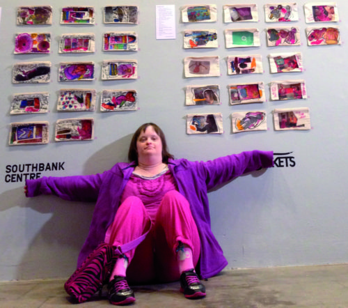 Learning-disabled artists sits against a wall filled with her artworks